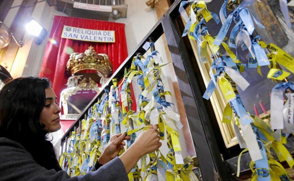 Chica colgando una cinta de los enamorados en la iglesia de san antón en madrid