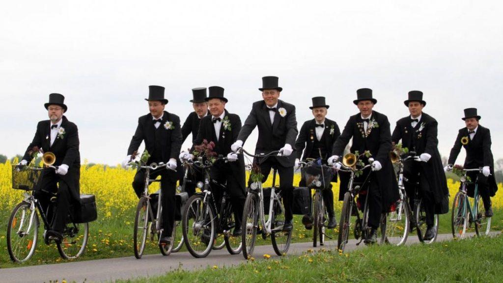 Celebración del Día del Padre en Alemania hombres vestidos con chaqué circulando en bicicleta
