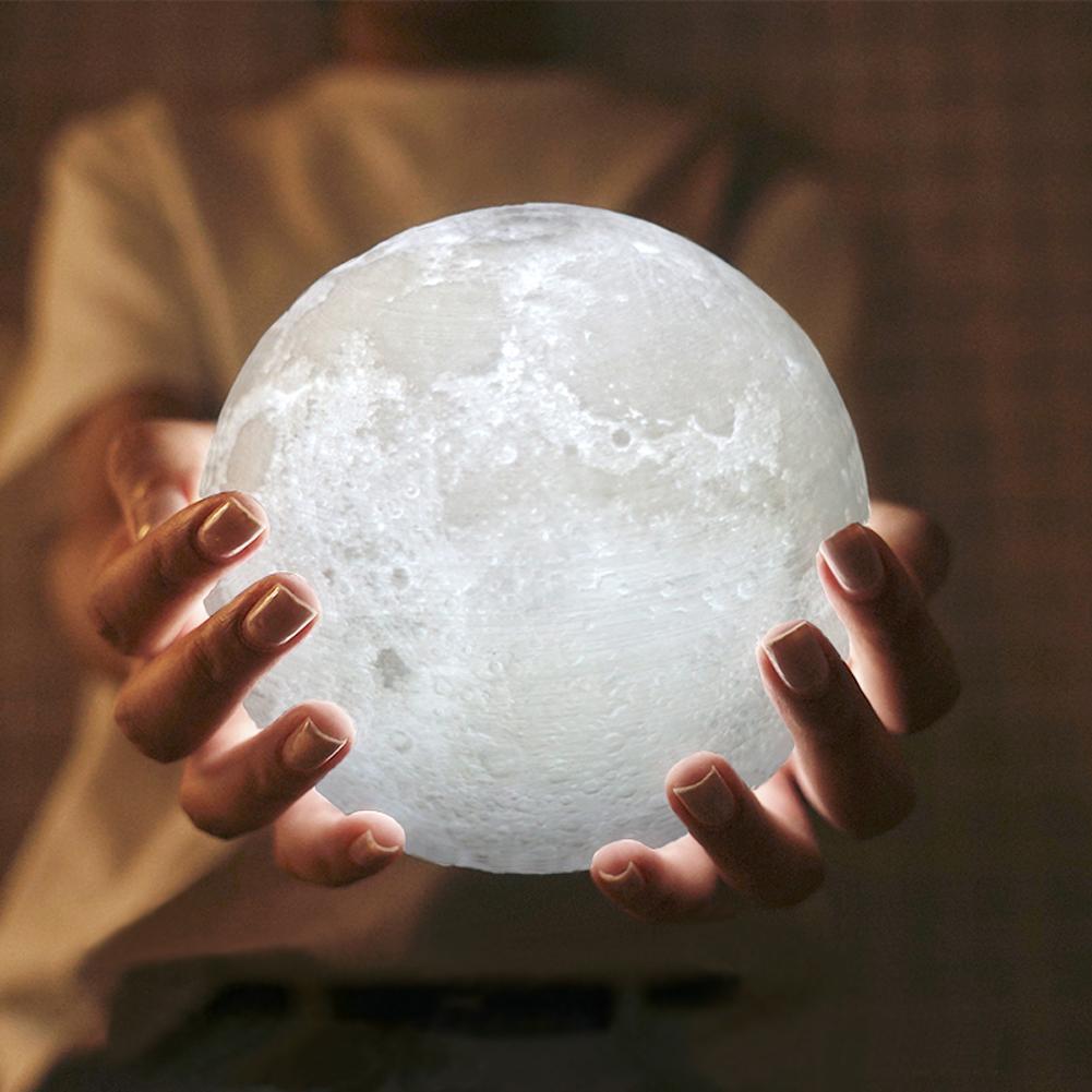Lámpara con forma de luna sostenida en las manos