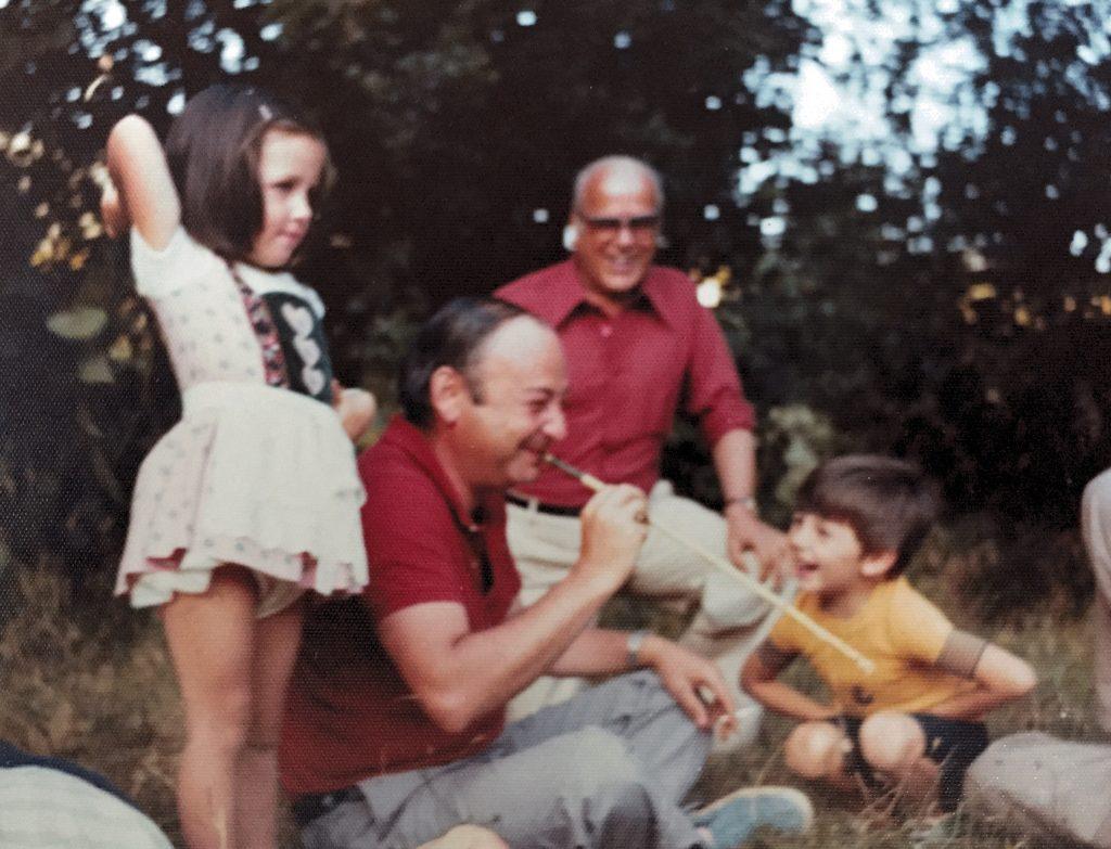 Padre enseñando a sus hijos a tirar con cerbatana en los años setenta
