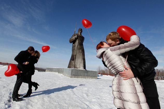 parejas de san valentin besándose en la nieve con globos en forma de corazón