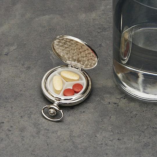 Un pastillero elegante con forma de reloj de bolsillo
